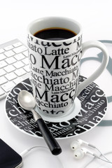 Black and white coffee mug with mobile and headphones