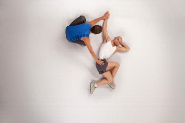athletic man streching with personal trainer