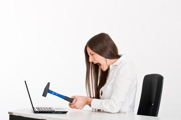 Frau zertrümert Notebook mit dem Hammer
