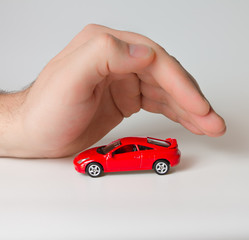 little red sports car under the man's hand