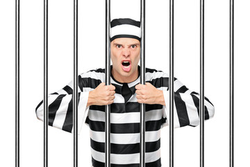 An agitated prisoner in jail holding bars