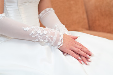 Women's hands on a white wedding dress. Bride seating