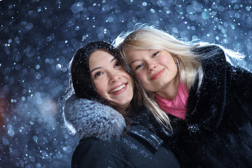 Girls enjoying winter on Christmas night snow background