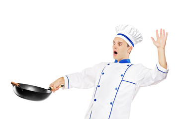 A surprised chef holding a wok