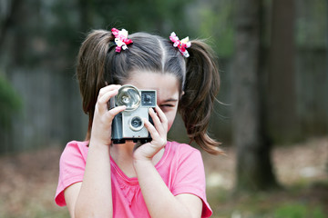 Cute little eight year old girl  with old vintage camera
