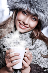 Girl blowing on hot drink dressed in winter clothing