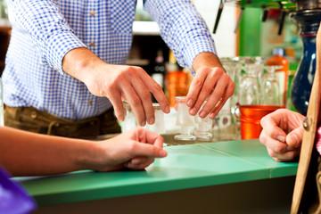 Barkeeper packt Schnapsgläser auf Bar