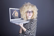 Portrait of funny girl in blonde wig with laptop