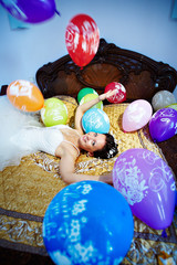 Happy bride plays with festive balloons
