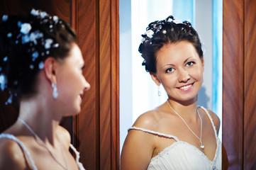 Happy bride near mirror
