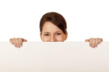 Junge glückliche Frau versteckt hinter leerer Werbetafel
