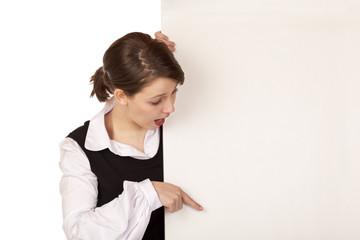 Überraschte junge Frau zeigt mit Finger auf leeres Schild