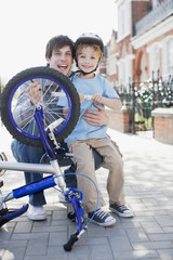 smiling father and son fixing bicycle tire on sidewalk