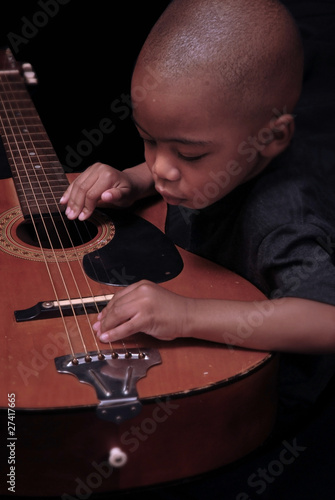 little boy plays the guitar
