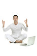 man dressed in white sitting on the floor with laptop