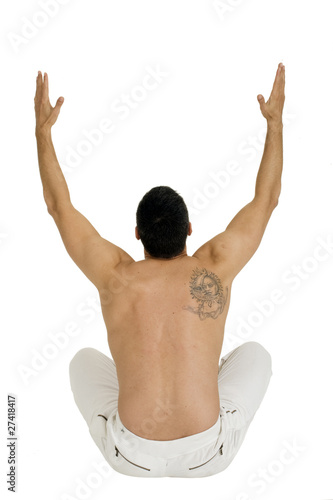 bare-chested man sitting on the floor with arms up