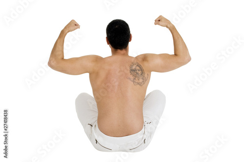 bare-chested man sitting on the floor shows the biceps