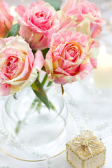 Bouguet of pink roses in vase,candle and little gift box