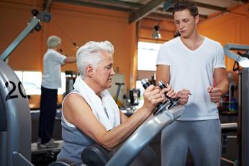 Seniorin bekommt Anleitung von Trainer
