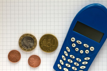 Coins, electronic calculator and squared paper
