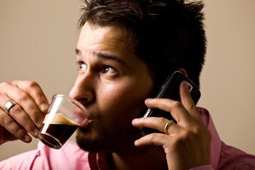 Uomo che beve un caffè mentre telefna