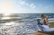 blond girl using laptop on  sea