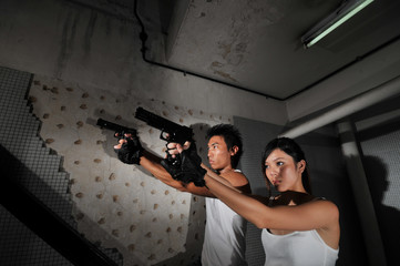 asian chinese couple carrying guns in staircase