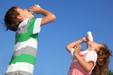 Small boy and the girl against sky, with pleasure drink yoghurt