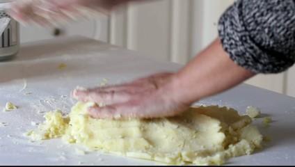 Mani che impastano patate e farina