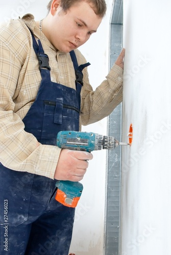 Young man drill a wall for installing power socket.