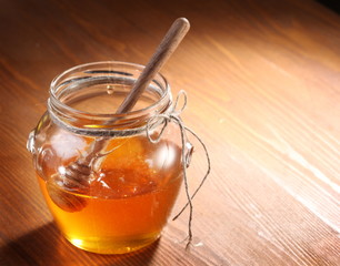 Pot of honey and wooden in it.