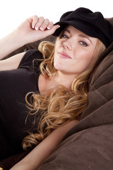 Woman on bean bag holding hat