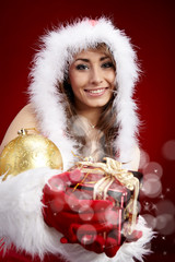 winter portrait of a beautiful young smiling woman with a gift i