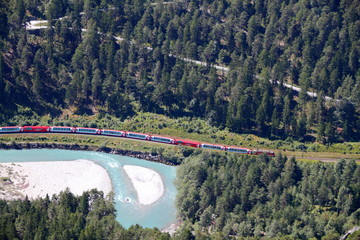 train Glacier Express drives alongside river Rhine in canyon