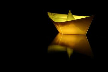 Einsames Papierschiff auf schwarzem Ozean