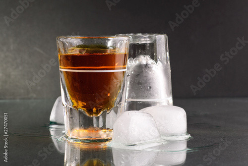 Shot of Whiskey with Ice Melting on Glass