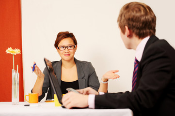 Couple in business meeting, young woman gestures