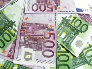Background of scattered 100 and 500 euro banknotes, close-up