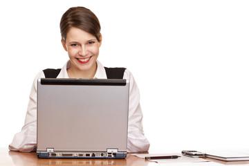 Junge lachende Geschäftsfrau sitzt im Büro und arbeitet an Lapto