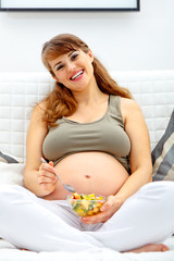 Beautiful pregnant woman on sofa with fruit salad in hand.