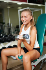 Women lifting free weights with a smile