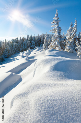 Plexiglas Heuvel Snowdrifts on winter snow covered mountainside and sun