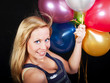 smiling woman on party holding balloons
