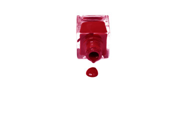 red nail polish bottle with splatters isolated on white backgrou