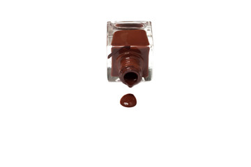 brown nail polish bottle with splatters isolated on white backgr