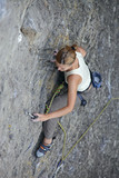 Female rock climber clinging to a cliff on her way up to the top