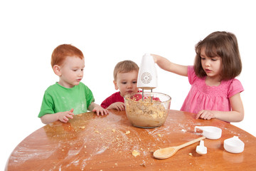 Kids baking cookies with electric mixer