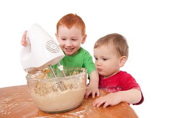 Boys baking cookies with electric mixer