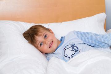 Kind liegt im Bett im Schlafzimmer