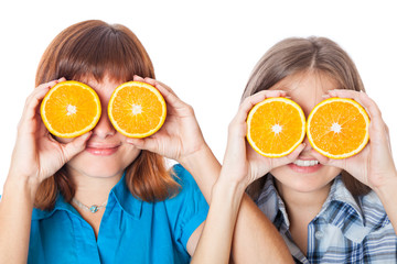 Two girls are looking through oranges